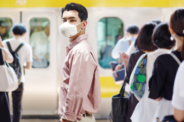 A man protecting himself by wearing the newest LG PuriCare Wearable in a subway station