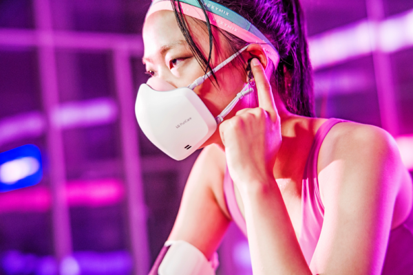 A woman wearing the newest LG PuriCare Wearable during a workout