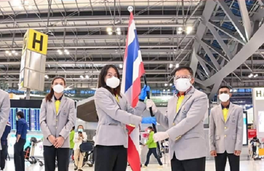 Thai athletes, coaches and staff wearing LG PuriCare Wearable while holding Thailand's national flag at Bangkok's Suvannabhumi Airport.