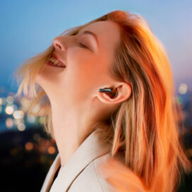 A stylish woman experiencing the immersive sound of LG's Charcoal Black TONE Free FP8 while outdoors