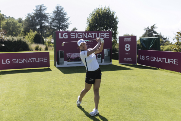 Professional golfer Ko Jin-young tees off in front of LG SIGNATURE signage.