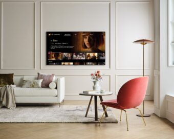 A wall-mounted LG TV in a modern living room displaying LG Channels with the movie 'In Time' on its Watch Now page