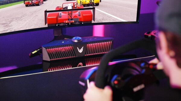 A gamer playing a game on an LG UltraGear gaming monitor connected to an LG UltraGear Gaming Speaker (model GP9).