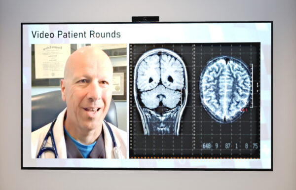 An image of video patient round - A screen displaying a X-ray result and a doctor