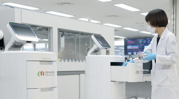 A scientist working with the help of LG CLOi ServeBot in the lab.