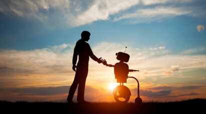 A human and a robot shaking hands during the sunset.
