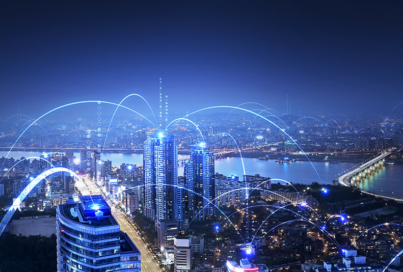 A city skyline at night with buildings connected with blue light to depict telecommunication technology.