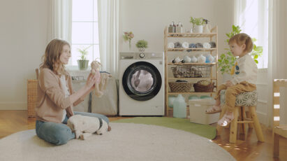 A mom playing with her daughter in the laundry room with LG washer running behind.