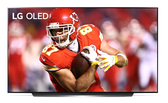 Image of Kansas City Chiefs' Travis Kelce shielding the football during a game displayed on LG OLED TV.