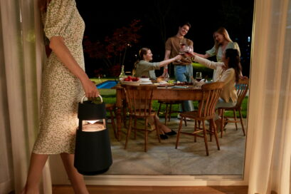 A woman carrying LG XBOOM 360 into the backyard for a party held during the night