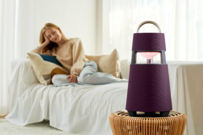 A woman relaxing on the sofa of a cozy living room as LG XBOOM 360 blends perfectly into the interior on top a small rattan table