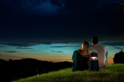 A couple enjoying the sunset on a grass hill with LG XBOOM 360 speaker behind them adding to the calm ambience
