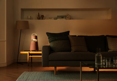 LG XBOOM 360 speaker on the side table of a dark living room as it gives off sun-like light