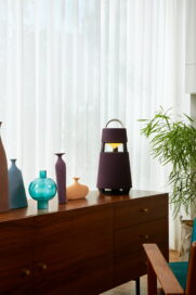 LG XBOOM 360 speaker blending with decorative objects on a wooden cabinet, its light matching the warm sunlight from outside