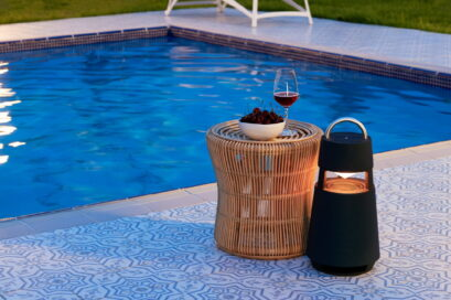 LG XBOOM 360 speaker poolside next to a rattan table with wine and fruit